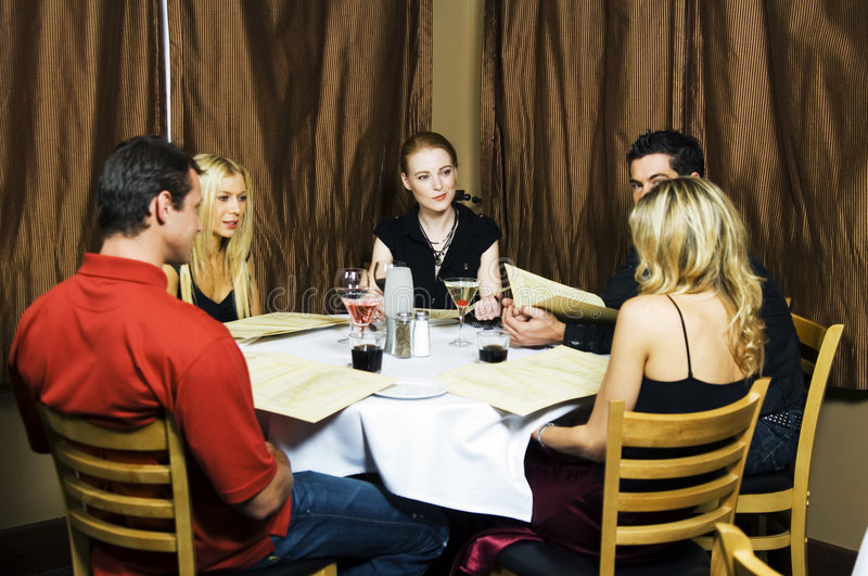 Restaurant scene. Group of young professionals in restaurant having dinner together, serving wine and checking out the menu to place their order royalty free stock photo