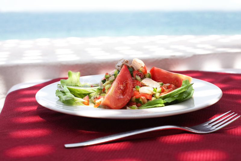 Restaurant with sea view. Salad from tunny and fresh vegetables in restaurant on open air with sea view stock photos