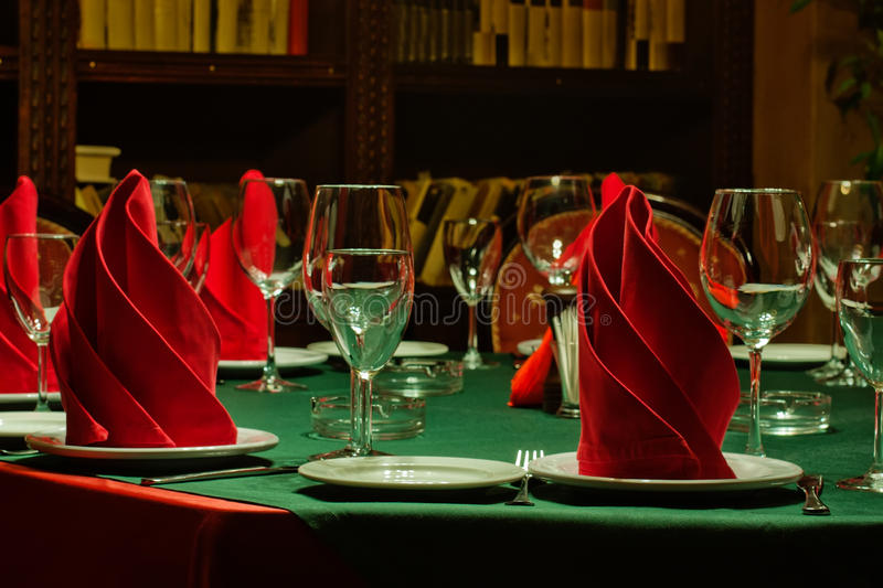 Restaurant service served table wine glasses and plate. Green tablecloth, red napkins, crockery and cutlery. royalty free stock images