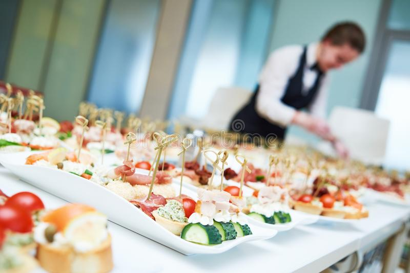 Restaurant waitress serving table with food. Restaurant service or waiter occupation. Female waitress worker serving table with food plates at catering in cafe royalty free stock photo