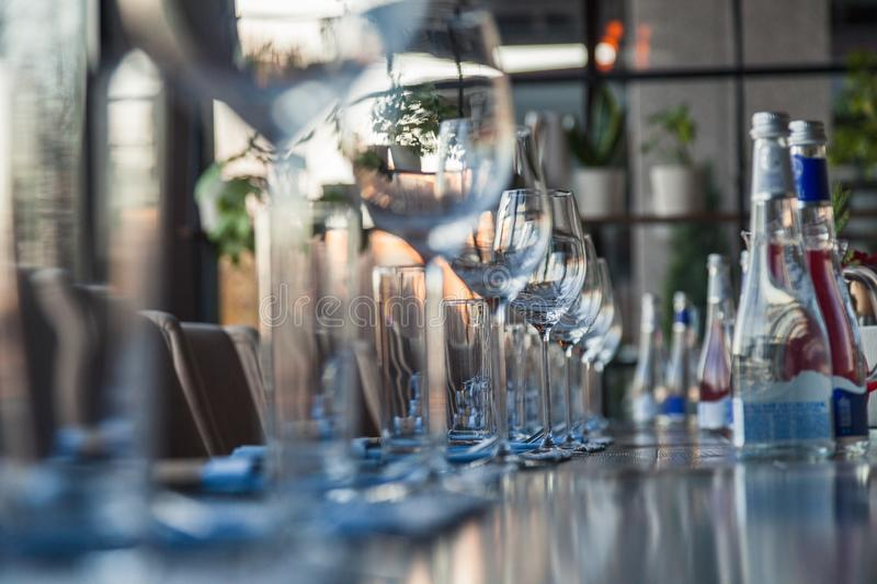Restaurant serving, glass wine and water glasses, forks and knives on textile napkins stand in a row on a gray wooden table. The stock photo