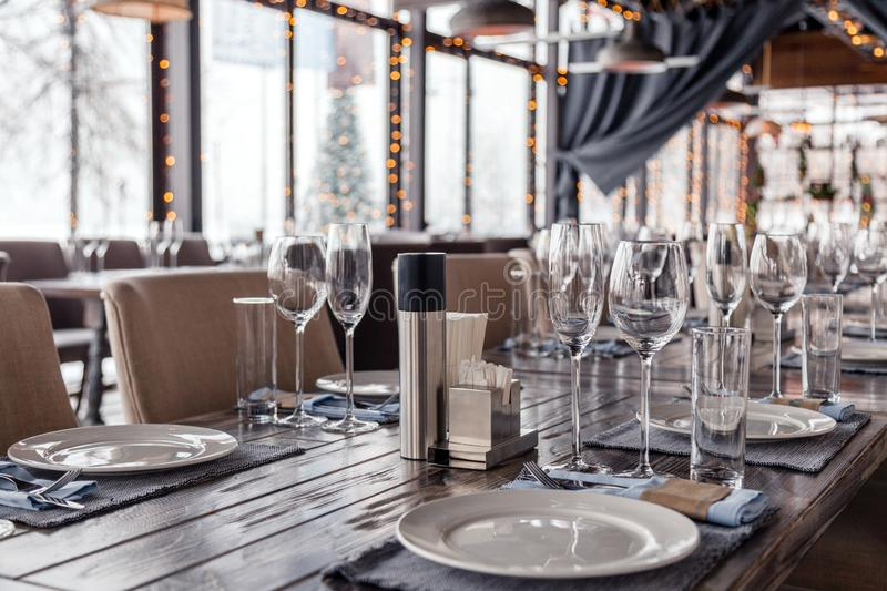 Restaurant serving, glass wine and water glasses, plates, spice set, forks and knives on textile napkins stand in a row on gray royalty free stock images