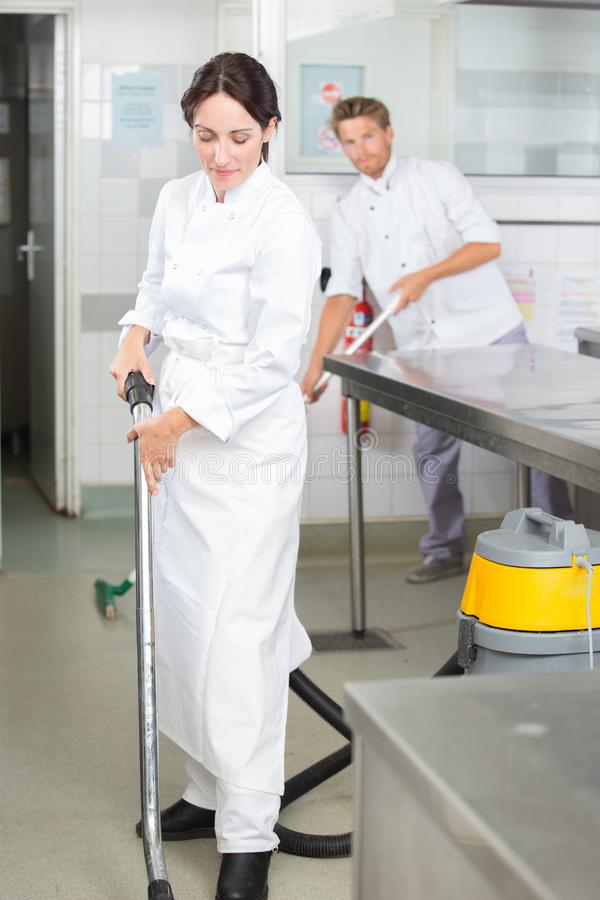 Restaurant staff cleaning kitchen floor after service. Kitchen royalty free stock image