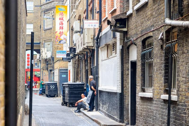 Restaurant staff having a break on the back street of London Chinatown royalty free stock image