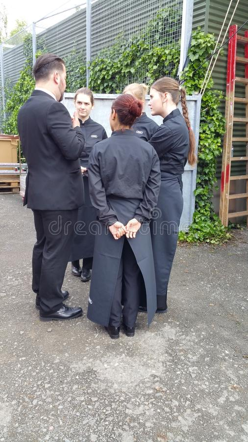 Restaurant staff having briefing meeting. Young female restaurant staff dressed in fashionable black with long black aprons at motor show having briefing meeting royalty free stock photos