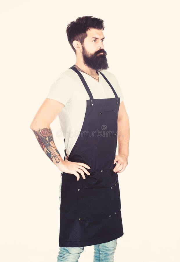 Restaurant staff. Waiter or bartender. Ready serve drink. Bearded hipster wear apron. Man cook brutal hipster. Serious stock images