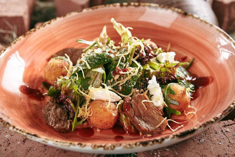 Duck Breast Salad with Crispy Potato Balls on Rustic Style Hay B stock images