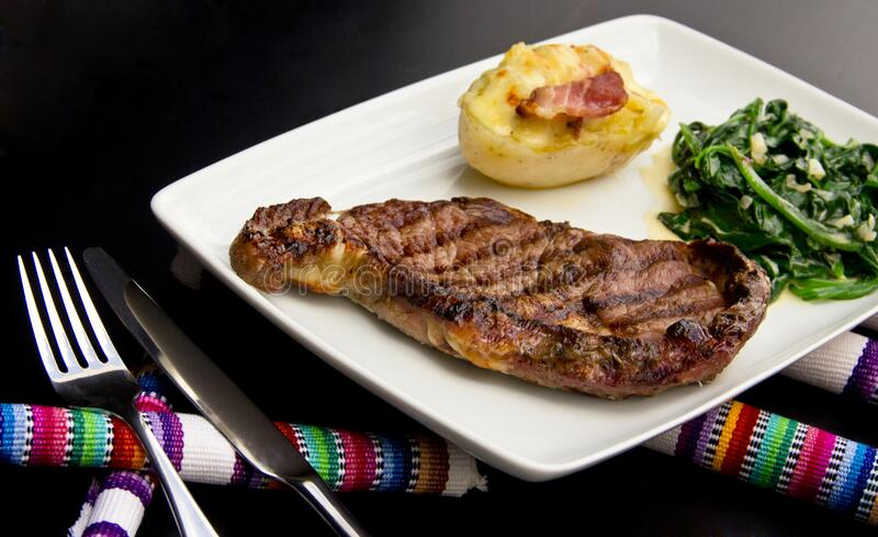 Restaurant Steak with stuffed potato and creamy spinach royalty free stock photo