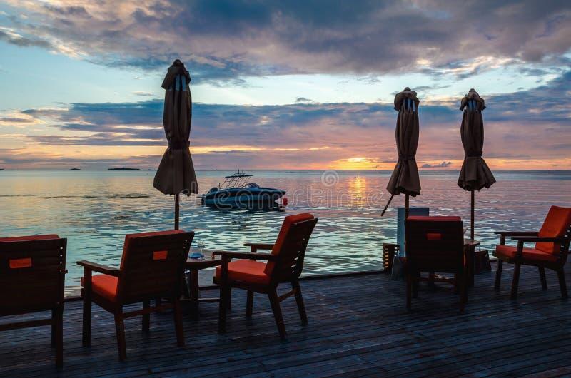 Restaurant sur l'eau sur le fond du beau coucher du soleil coloré au-dessus de l'océan photo stock