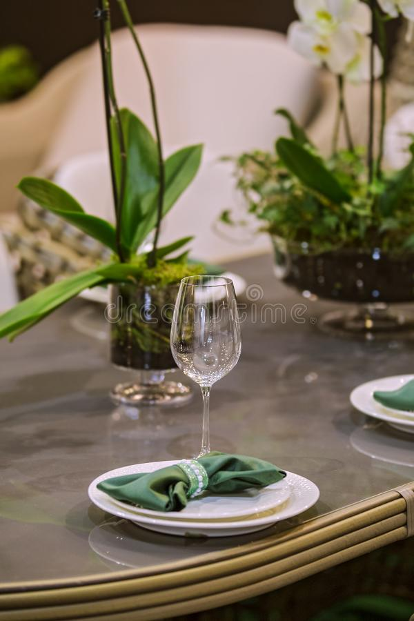 Restaurant table in eco style with green elements, wooden table, live orchids, glasses, plates, feast royalty free stock image