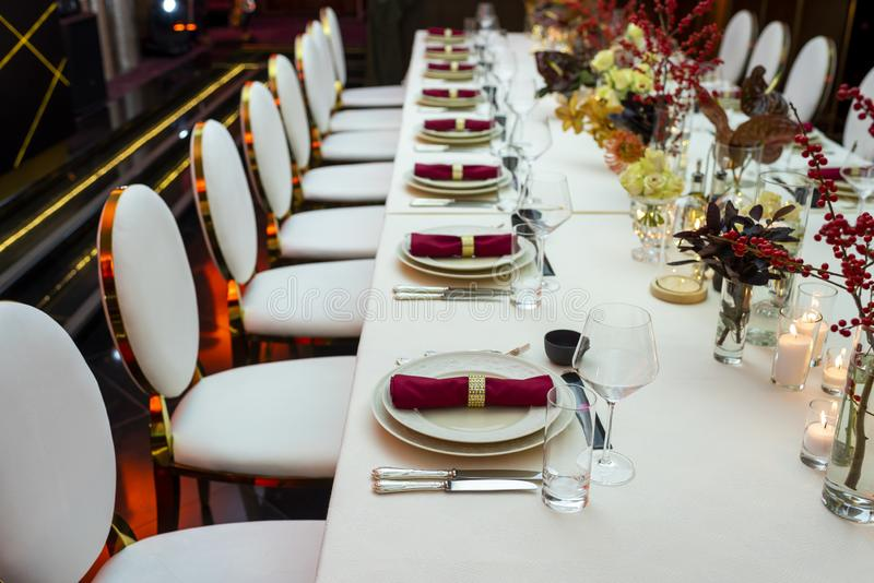 Restaurant table with napkins and wine glasses. Perspective decorated table in a restaurant with plates and napkins and wine glasses decorated with flowers stock photos