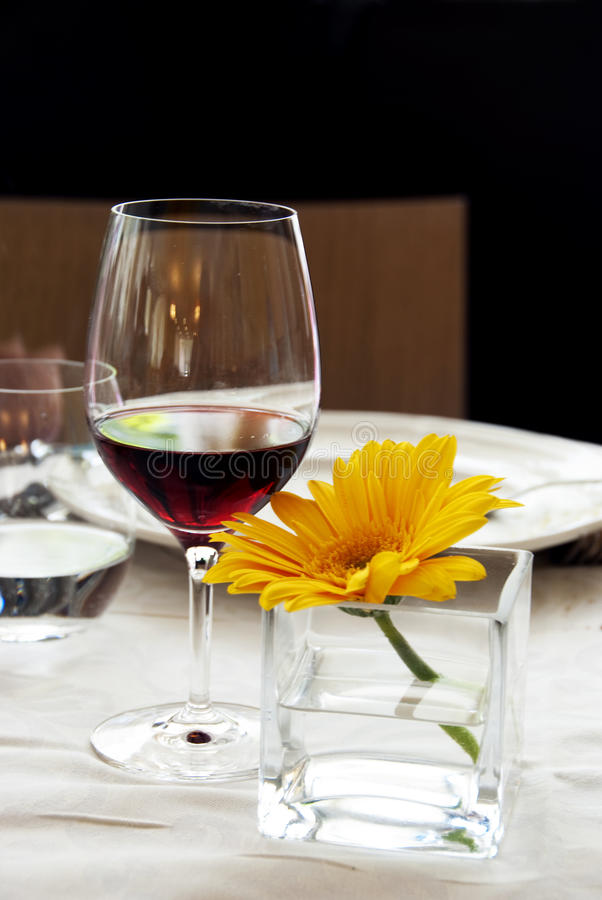 restaurant table red wine and yellow flower stock images