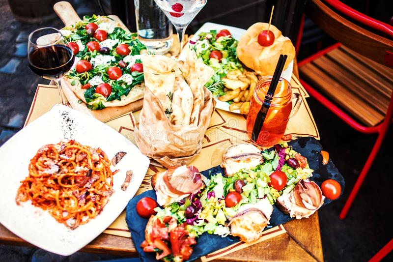 Restaurant table setting with food outdoor on the street. Italian pasta spaghetti, glass of red wine, mozarella cheese, bread, sa. Lad, tomatoes, burger and meat royalty free stock images