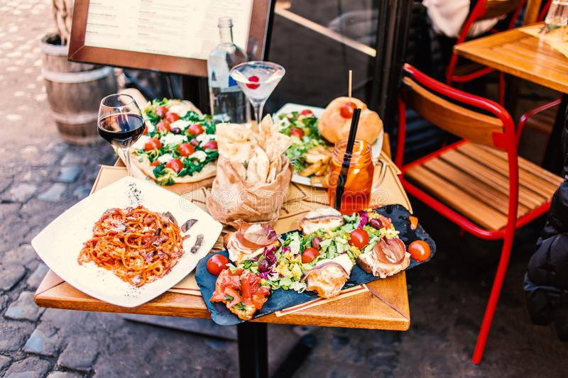 Restaurant table setting with food outdoor on the street. Italian pasta spaghetti, glass of red wine, mozarella cheese, bread, sa. Lad, tomatoes, burger and meat stock image