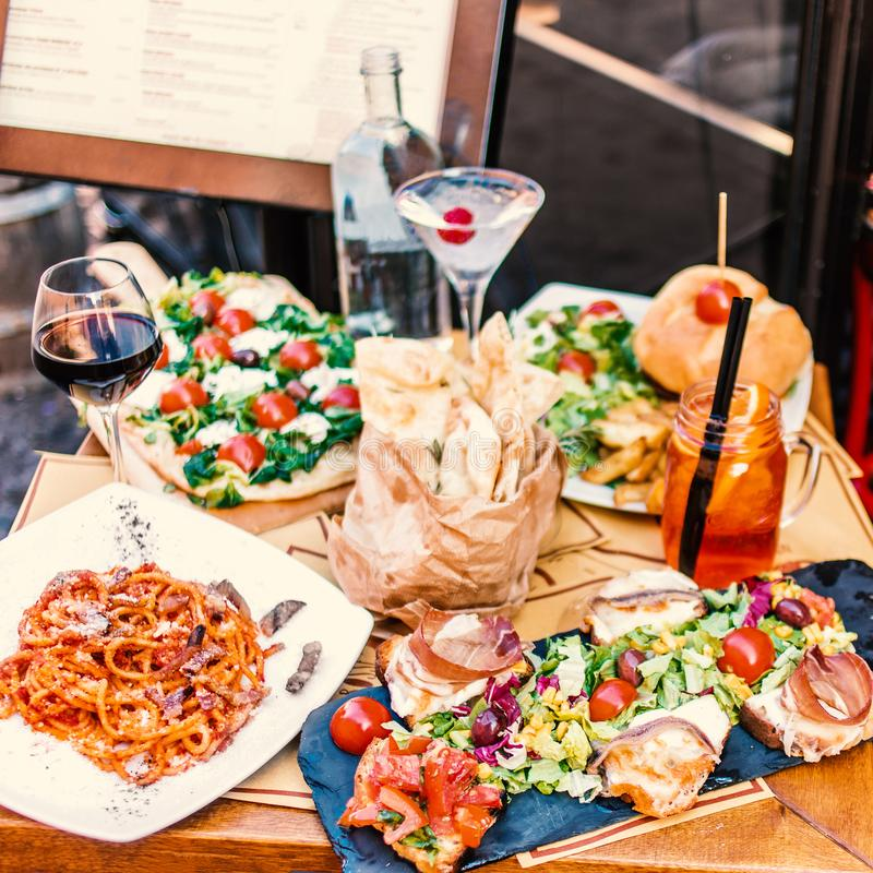 Restaurant table setting with food outdoor on the street. Italian pasta spaghetti, glass of red wine, mozarella cheese, bread, sa. Lad, tomatoes, burger and meat stock images