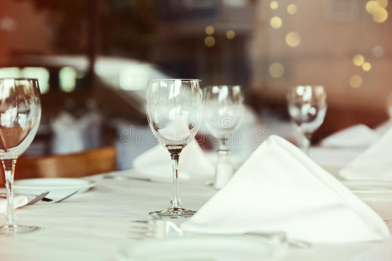 Restaurant table setting with wine glass. Selective focus on wine glass. Restaurant table setting with wine glass over blur background. Selective focus on wine royalty free stock images