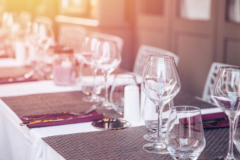Restaurant table setting, wine glasses and white plates. Glare of light.  stock images