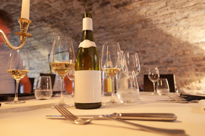 Restaurant table with vintage silverware, bottle of white wine with blank label, glasses, cutlery, gold candlestick, degustation royalty free stock images