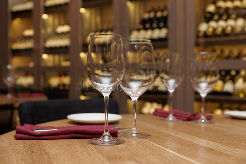 Restaurant table with wine fridge in the background. Restaurant table with wine cellar in blurred background royalty free stock photos