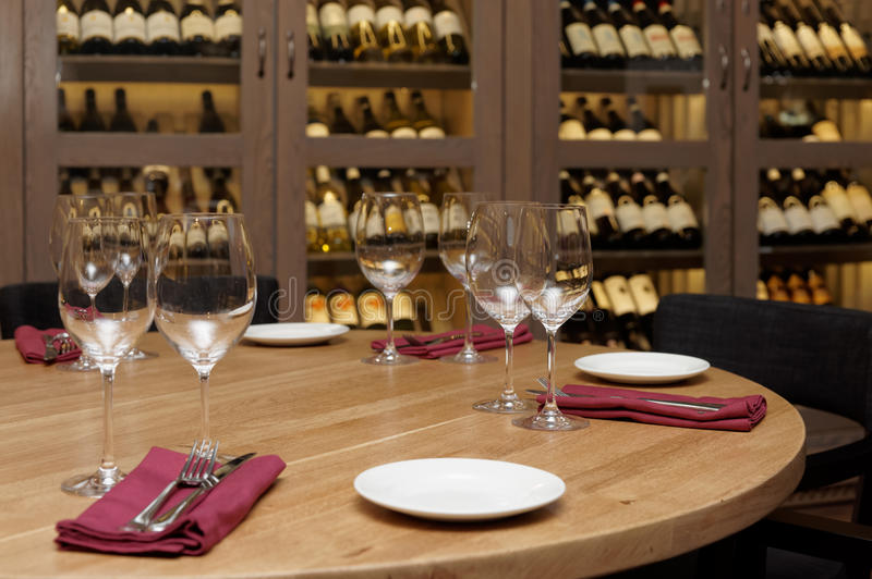 Restaurant table with wine fridge in the background. Restaurant table with wine cellar in blurred background stock photo