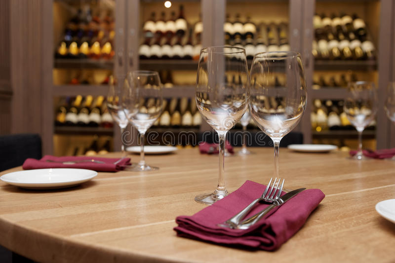 Restaurant table with wine fridge in the background. Restaurant table with wine cellar in blurred background stock photography
