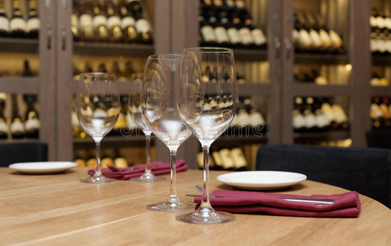 Restaurant table with wine fridge in the background. Restaurant table with wine cellar in blurred background royalty free stock image