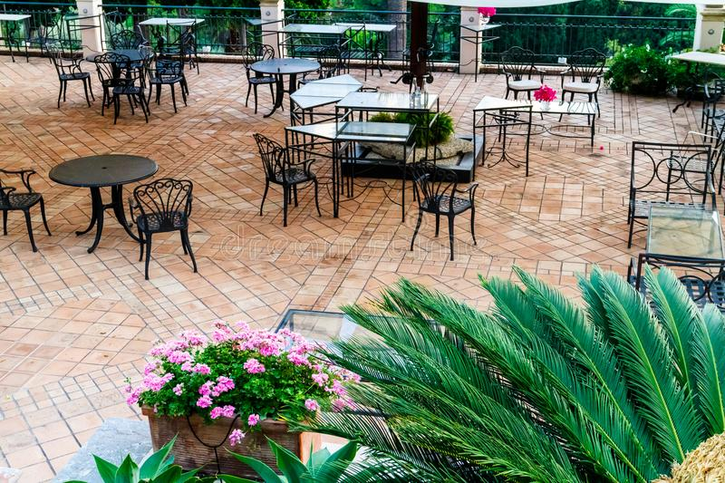 Restaurant tables and chairs on a brick patio. Vacant empty restaurant tables and chairs on a brick patio with ferns and flowers in pots viewed high angle royalty free stock photos