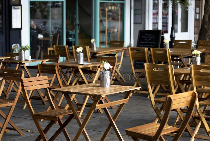 Restaurant tables and chairs. Empty wooden tables and chairs outside city centre restaurant with shallow depth of field royalty free stock photos