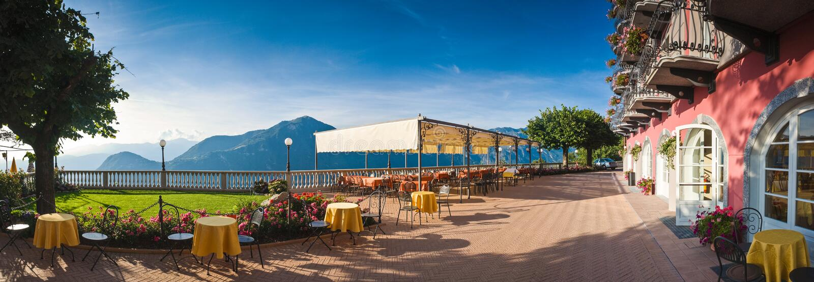 Restaurant with a view. Pretty restaurant tables with a stunning Italian mountain view royalty free stock photography