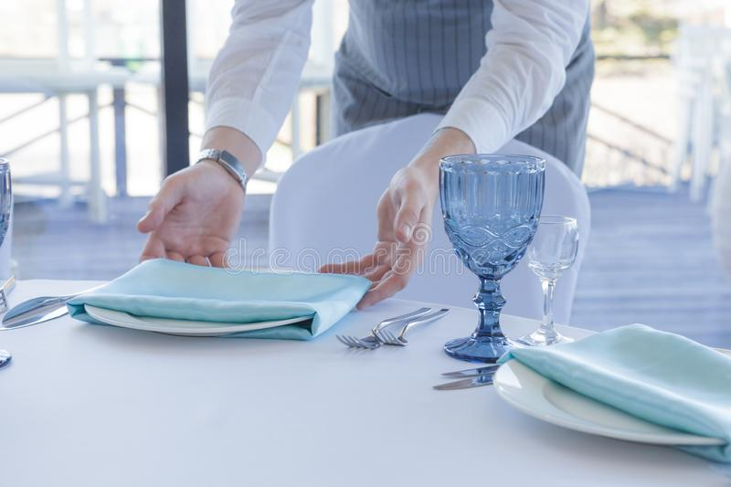 Restaurant waiter serves a table for a wedding celebration royalty free stock photography