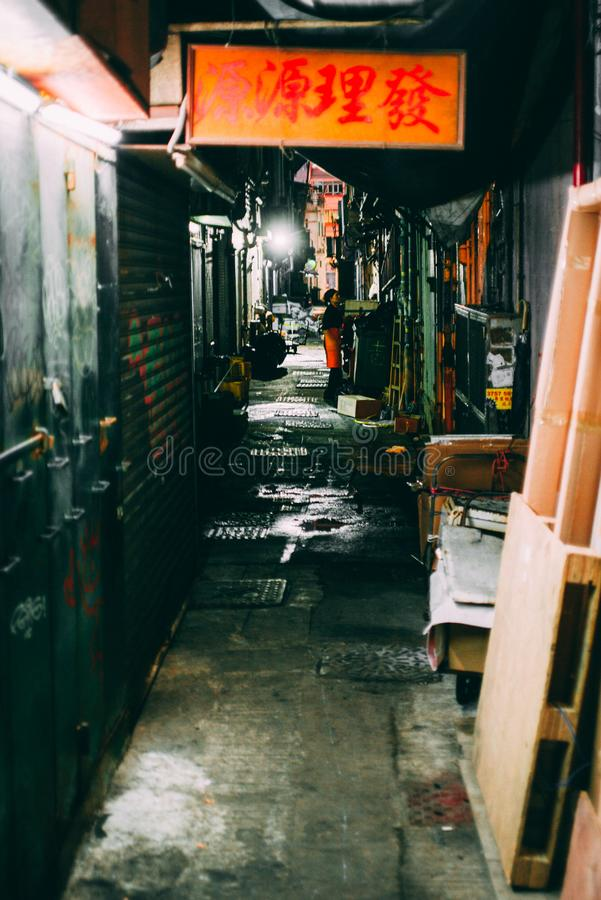 A restaurant waitress in a dark alley in Hong Kong royalty free stock photography