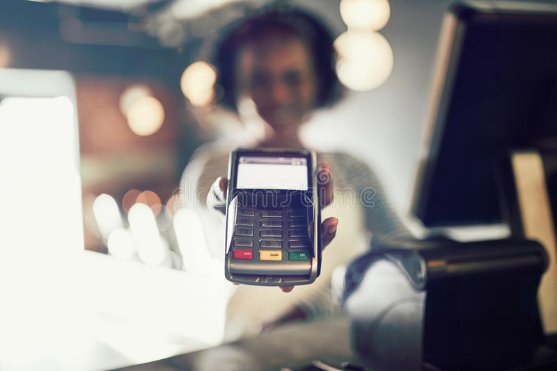 Restaurant waitress holding an electronic card payment machine royalty free stock photos