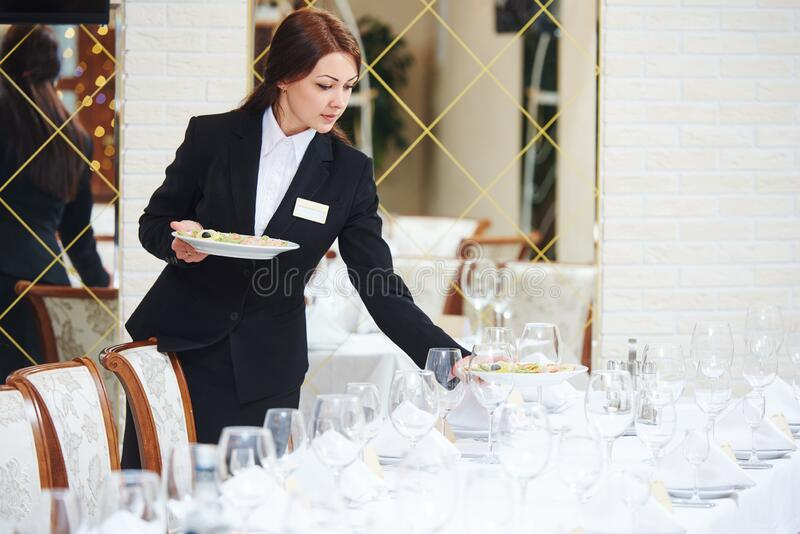 Restaurant waitress serving table with food. Restaurant service or waiter occupation. Female waitress worker serving table with food plates at catering in cafe stock photos
