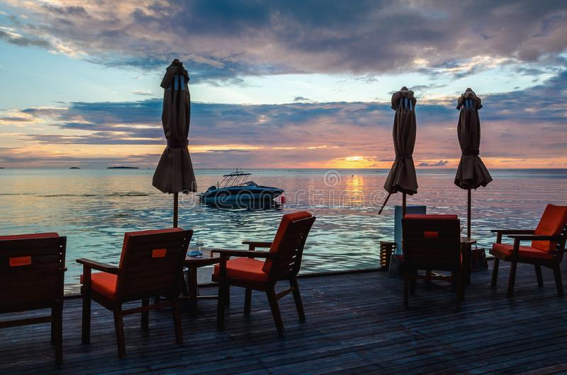 Restaurant on the water on the background of beautiful colorful sunset over the ocean stock photo