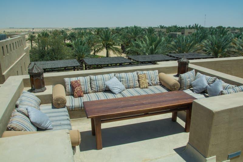 Restaurantaufenthaltsraum im Freien auf die Dachoberseite mit Sofatabelle und bequemen Kissen am Wüstenluxus-resort stockfoto