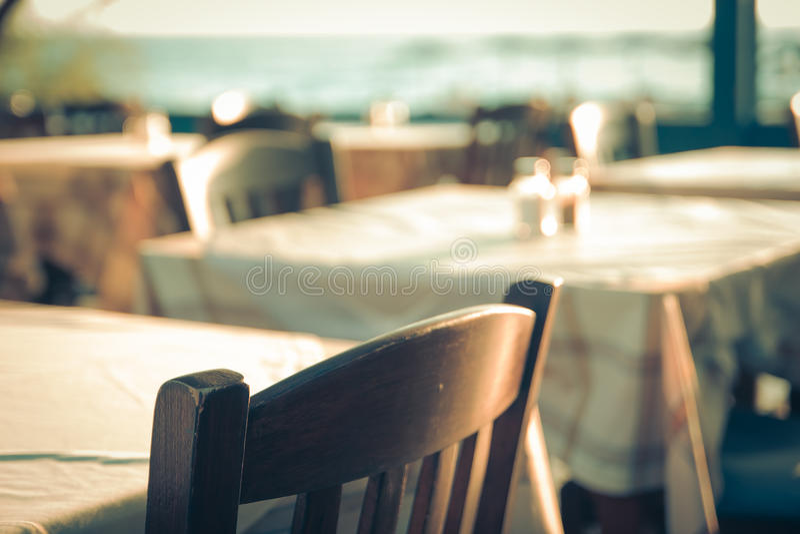 Restaurante al aire libre griego tradicional en el mar Mediterráneo de desatención de la terraza (Grecia) tabla vacía en un mar d fotografía de archivo libre de regalías