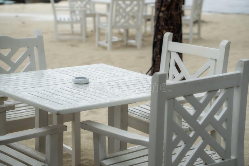 Restaurante branco da tabela na praia A estação das chuvas começou imagem de stock