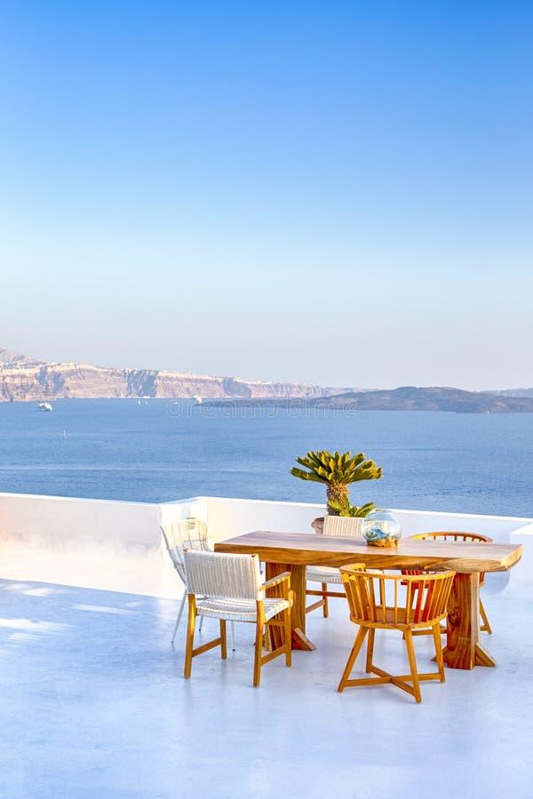 Restaurante confortável do terraço do ar livre tranquilo romântico na vila bonita de Oia na ilha de Santorini em Grécia antes do  fotografia de stock royalty free