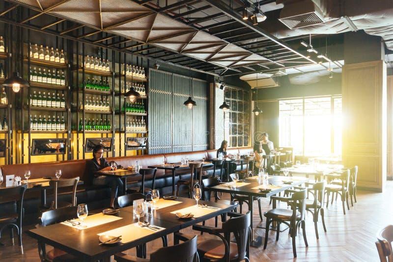 Restaurante de cena fino moderno adornado con el techo de acero y abierto con los clientes dentro en Bangkok, Tailandia foto de archivo