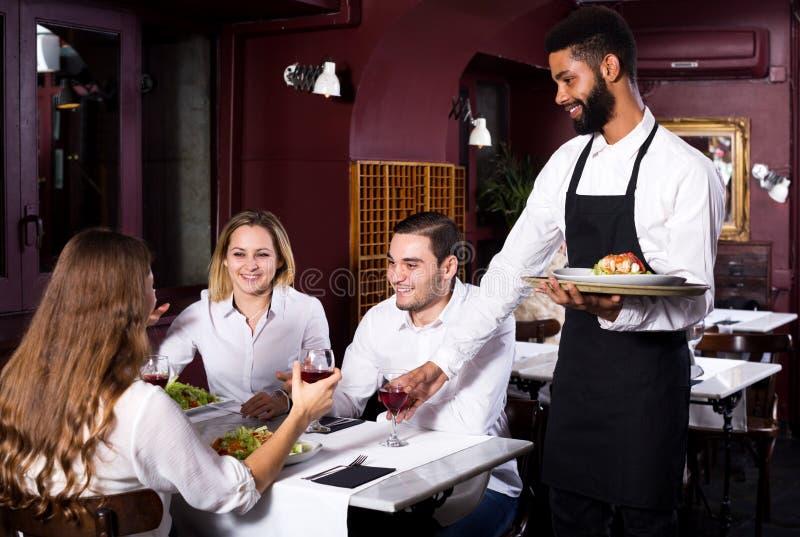 Restaurante de la clase media y camarero alegre imagen de archivo libre de regalías