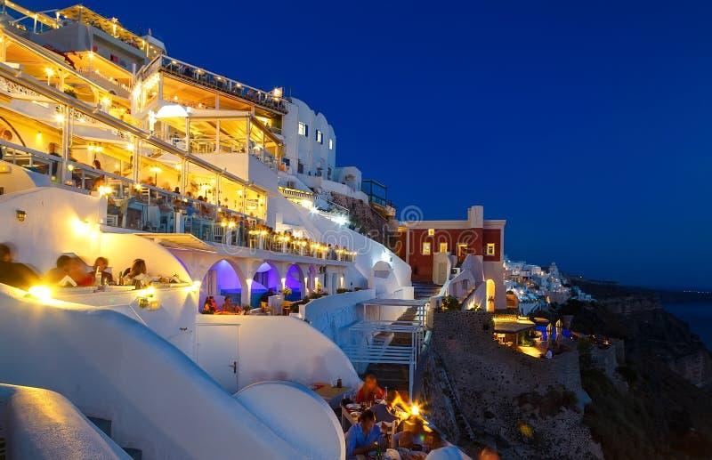 Restaurante de la noche con los turistas de Fira Santorini, el centro turístico europeo famoso, Grecia imagen de archivo