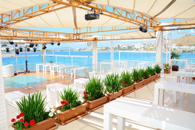 Restaurante del mar con las tablas de madera blancas y la opinión del mar fotos de archivo libres de regalías