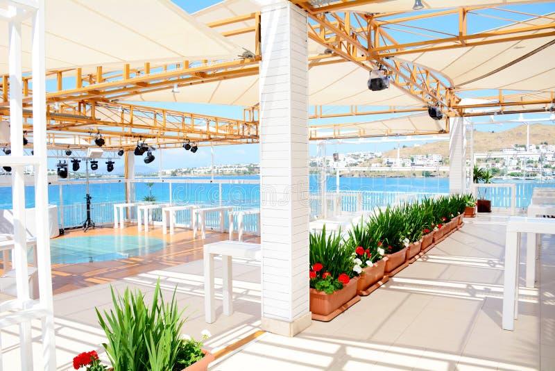 Restaurante del mar con las tablas de madera blancas y la opinión del mar imagenes de archivo
