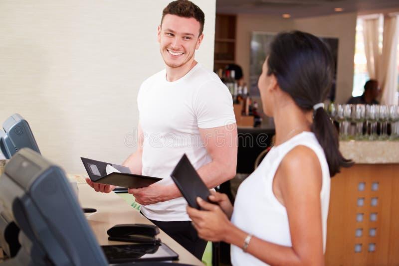 Restaurante do hotel de And Waitress In do garçom que prepara Bill imagem de stock royalty free