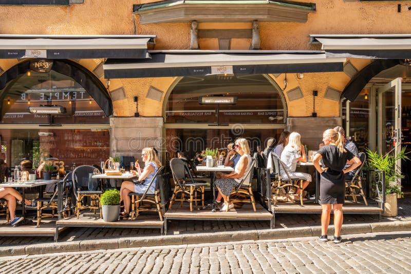 Restaurante exterior com muitos convidados que têm o jantar e uma empregada de mesa fêmea imagens de stock