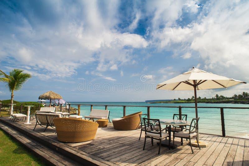 Restaurante exterior na praia. Café na praia, no oceano e no céu. Ajuste da tabela no restaurante tropical da praia. República Dom fotografia de stock royalty free