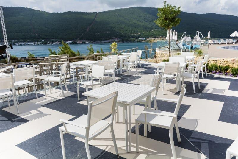 Restaurante griego acogedor con las tablas blancas y la opinión del mar imagen de archivo