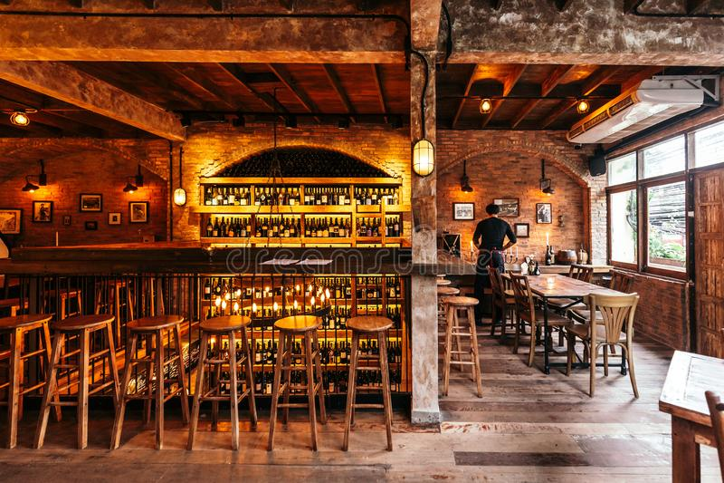 Restaurante italiano adornado con el ladrillo en la luz caliente que creó la atmósfera acogedora con el camarero en la tabla dere fotos de archivo libres de regalías