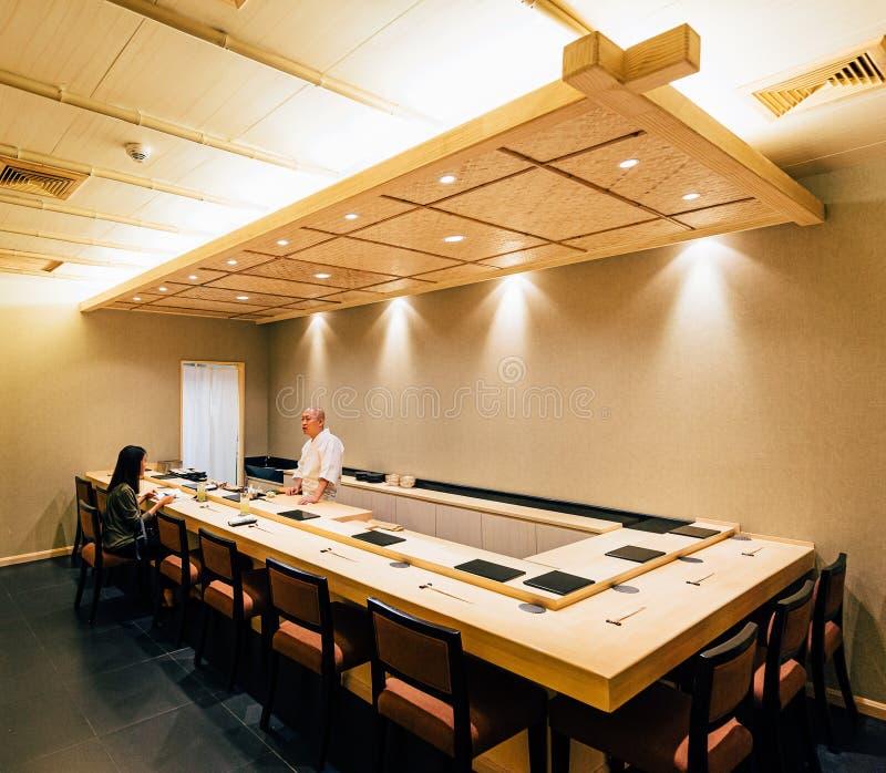 Restaurante japonês de Omakase que decorou na maior parte com madeira Cozinheiro chefe que cozinha em menus do contador e do saqu fotos de stock