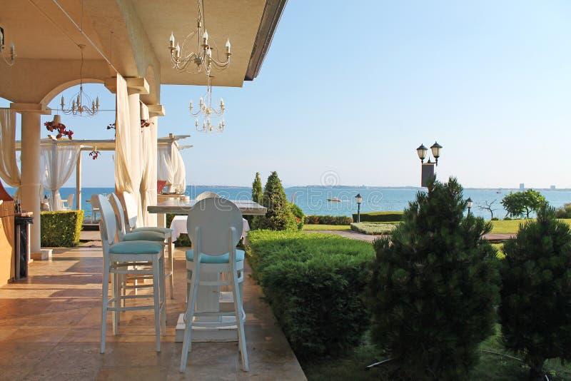 Restaurante que pasa por alto el mar y el jardín imágenes de archivo libres de regalías